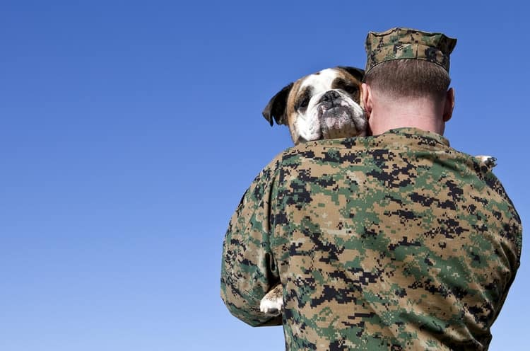 Military officer holding dog who has a military dog name